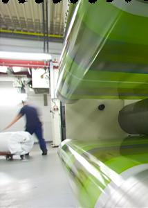 Langzeitbelichtetes Bild einer Druckmaschine mit Arbeiter im Hintergrund
