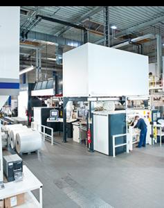Halle mit Maschinen an denen Menschen arbeiten